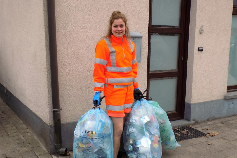 Ophaalster Annelien Jacobs van IOK Afvalbeheer verzamelt een hoeveelheid blauwe pmd-zakken in Beerse.