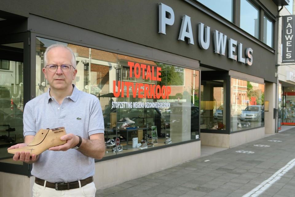 Zaakvoerder Joris Pauwels voor de brede winkel met een houten leest op basis waarvan zijn vader Walter destijds zelf een paar damesschoenen vervaardigde.