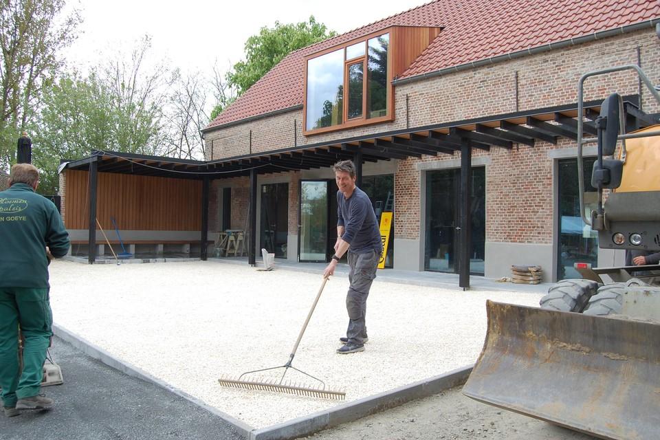 Kris legt eigenhandig het terras aan, dat zaterdag klaar moet staan.