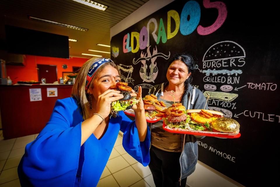 Donka Stankovski (rechts) met haar vers bereide hamburgers. Jobstudent Ibtissam Chabouni proeft er eentje.