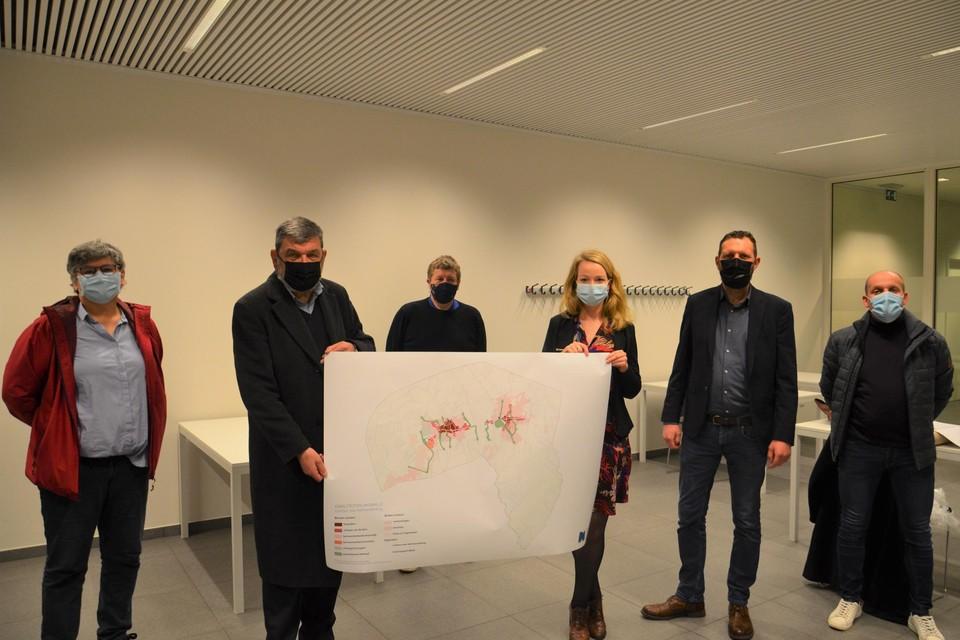Burgemeester Harry Hendrickx (DBM) en schepen voor Ruimtelijke ordening Sanne Van Looy (N-VA) tonen de kaart met de afbakeningen, temidden van de rest van het schepencollege.