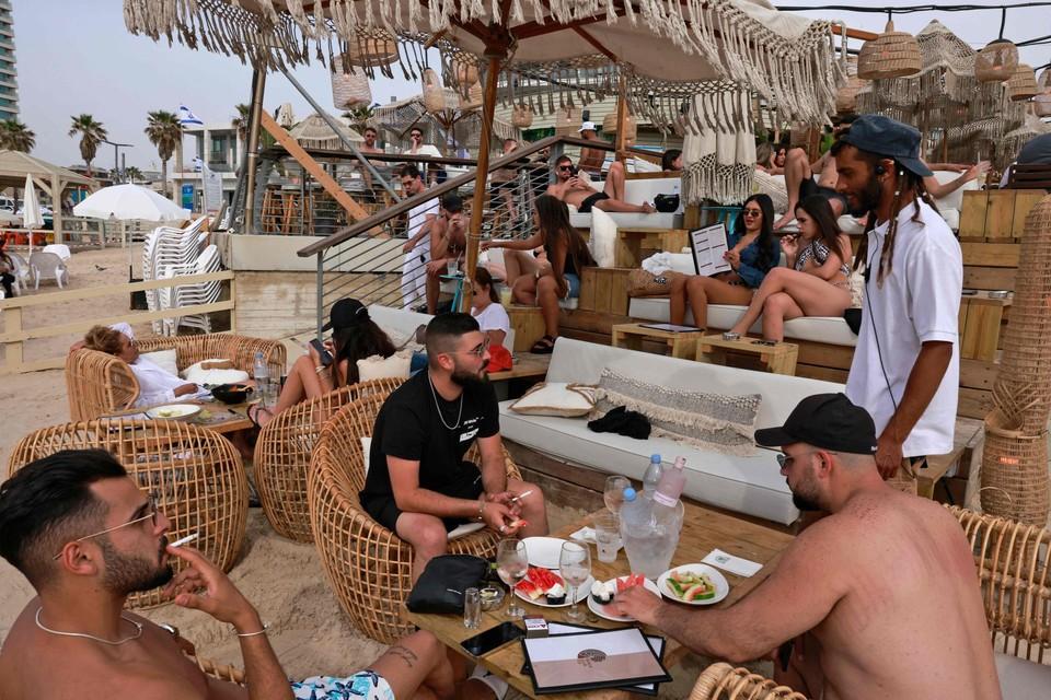 """In een strandbar in Tel Aviv zijn geen mondmaskers meer te zien. """"Wij leven in een tijdperk waarin corona veel minder belangrijk is. Op nieuwswebsites is het zoeken naar een bericht over corona."""""""