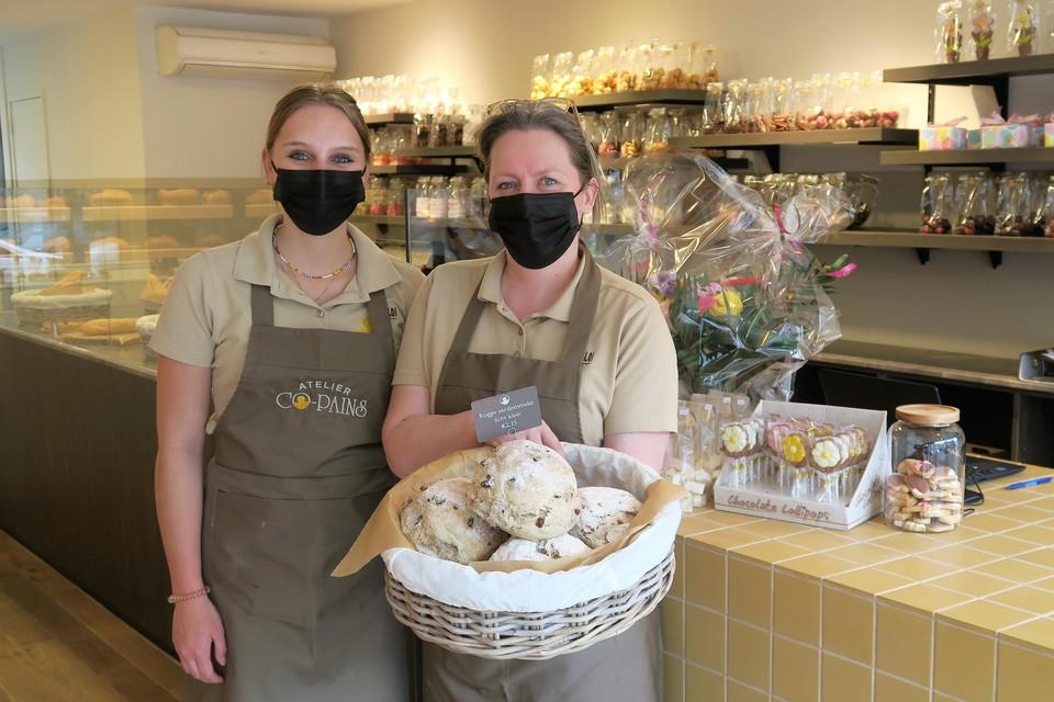 Karin Brughmans toont één van de succesnummers van de pas geopende bakkerij Atelier Co-Pains in 's-Gravenwezel: een mand vol 'roggeverdommekes'. Naast haar winkelmeisje Hanne Van Uffelen.