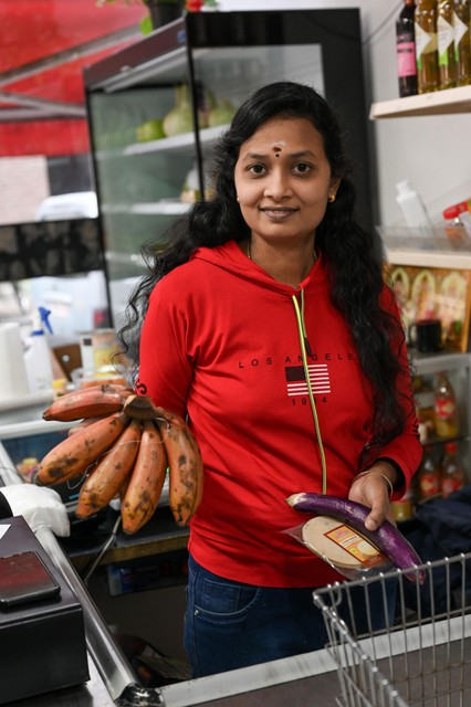 Een medewerkster van Euro Asians toont kleine, zoete banaantjes en een aubergine.