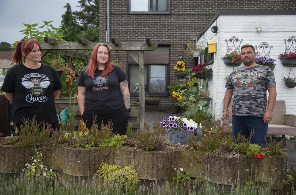 Mieke met haar dochter Gia en haar vriend Jimmy in hun kleurrijk tuintje in de wijk Brasel.