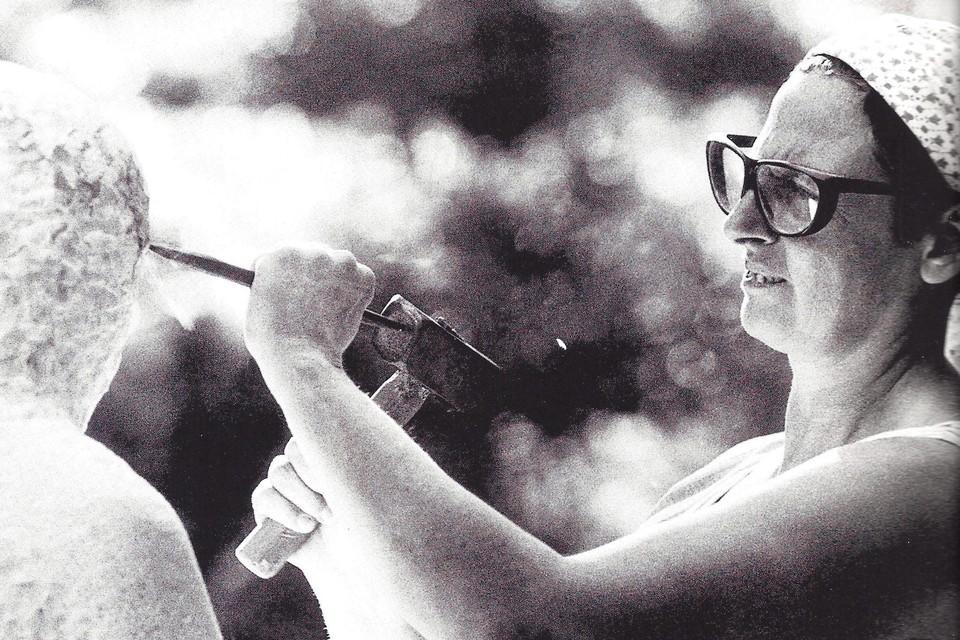 Mariette Coppens terwijl ze in carrarramarmer beeldhouwt.