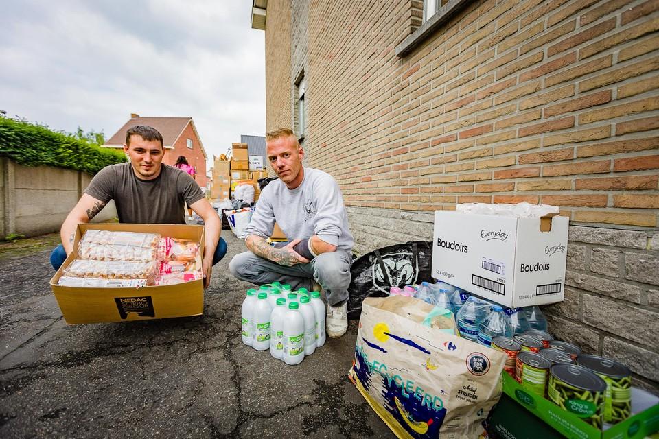 Kim Pelles en Bram Saele (met gips) tussen de ingezamelde hulpgoederen voor de inwoners van Pepinster.