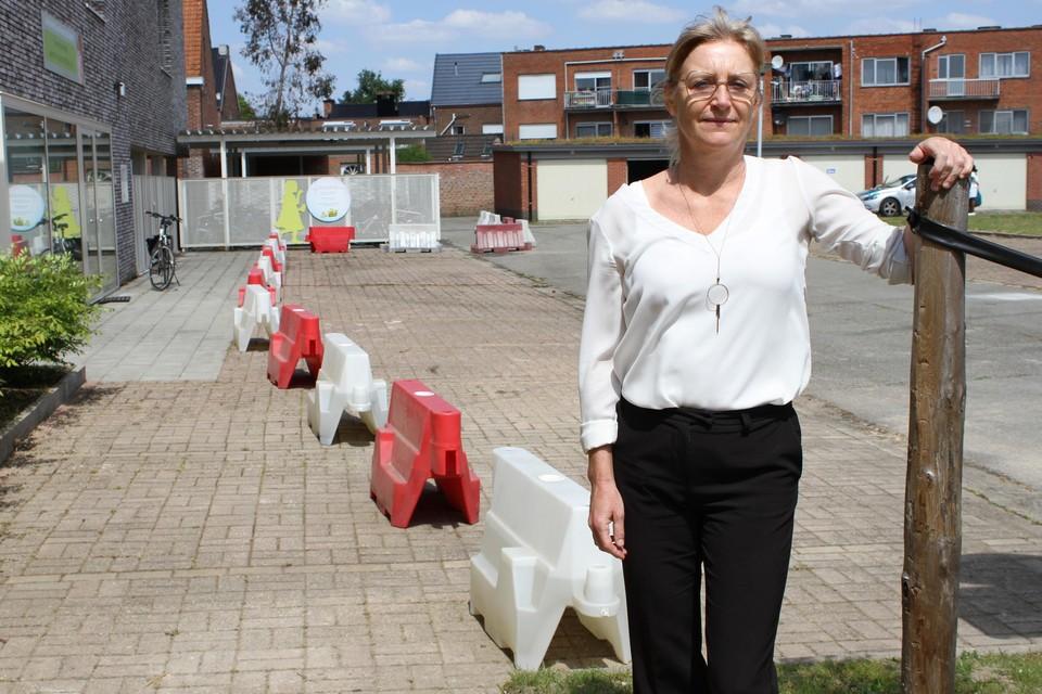 Schepen Ann Van Winkel staat aan de rood-witte new jerseys die de wandel- en fietszone afscheiden van de parkeerplaatsen en de rijweg.