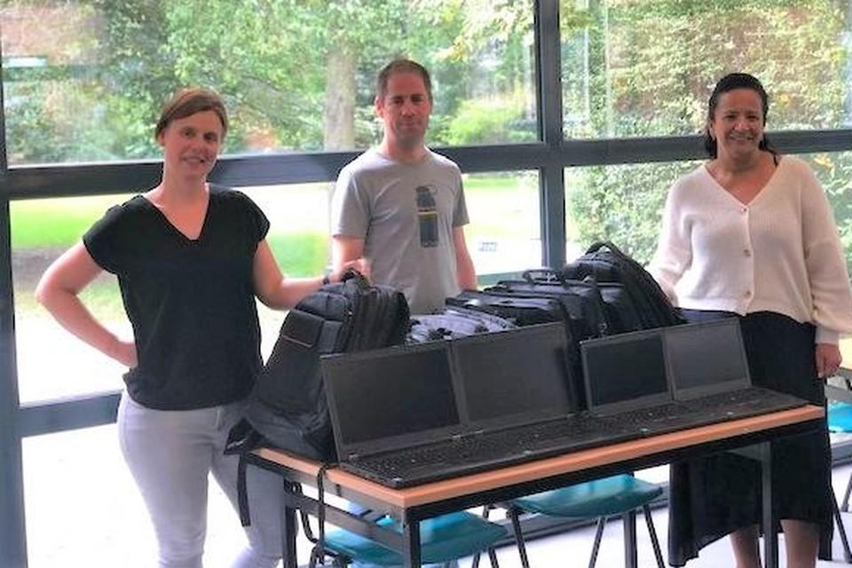 Ilse Verbruggen van De VoorZorg overhandigt de laptops aan Roel Noukens en Zineb El Boussaadani van J@M.